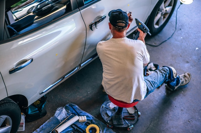 muž opravujúci auto