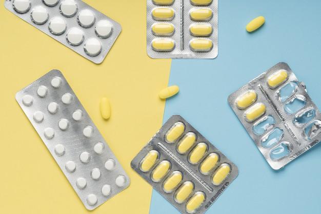 top-view-yellow-white-pills-blue-yellow-background_129454-209